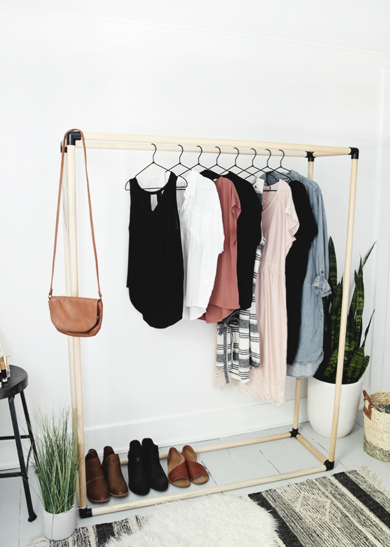 black and wood dowel clothing rack with clothes on it