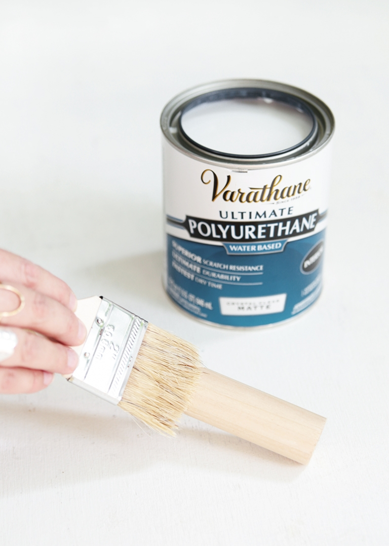 can of polyurethane and paint brush on dowel