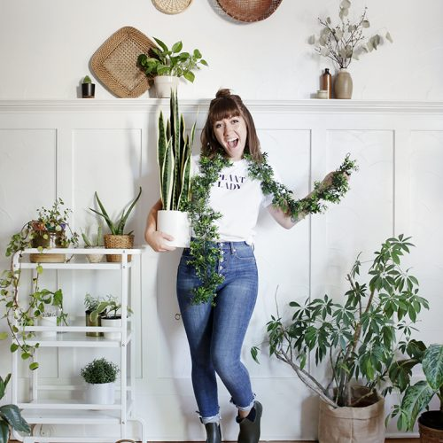 woman wearing plant lady costume surrounded by plants