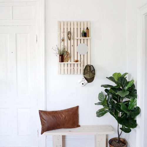 small entryway with wooden bench, wood slat wall shelf, and plant