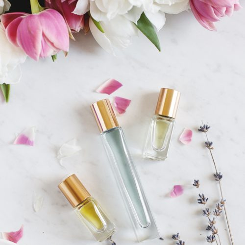 three glass perfume bottles with flowers
