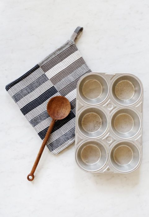 muffin tin and wooden spoon on top of striped potholder