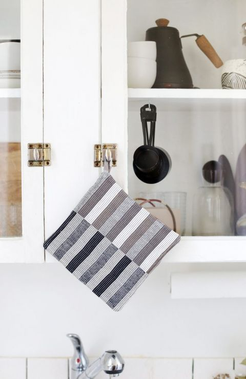 striped potholder hanging on kitchen cabinet