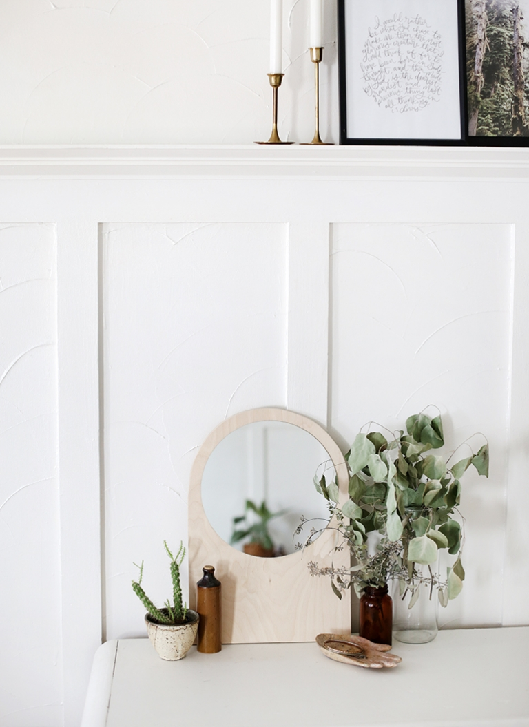 arched plywood mirror on dresser with dried eucalyptus