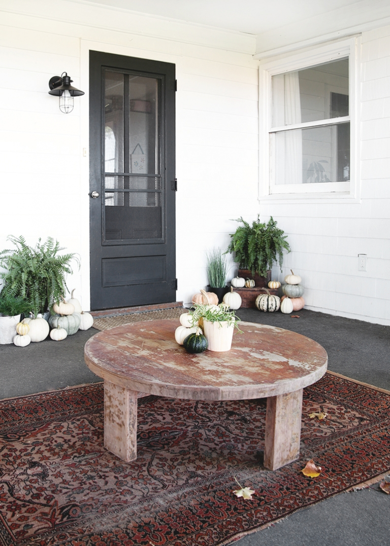 porch with vintage rug round table and pumpkins