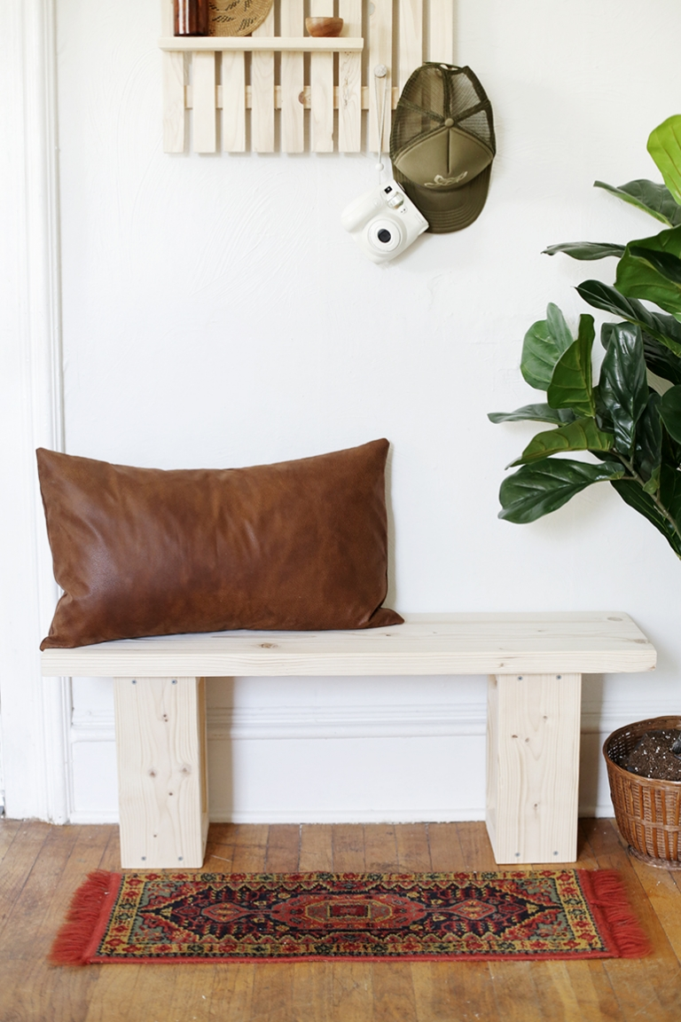 wooden bench against white wall with faux leather pillow