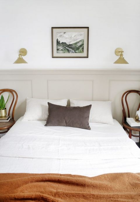 bedroom with taupe half wall and neutral decor pieces
