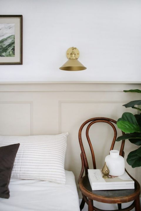 close up of wall sconce and chair nightstand