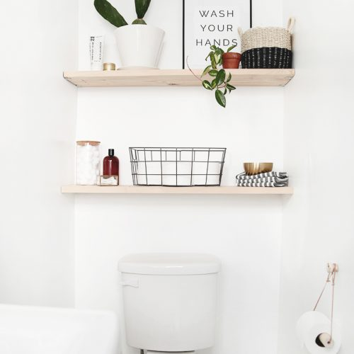 items on wood bathroom shelves above toilet