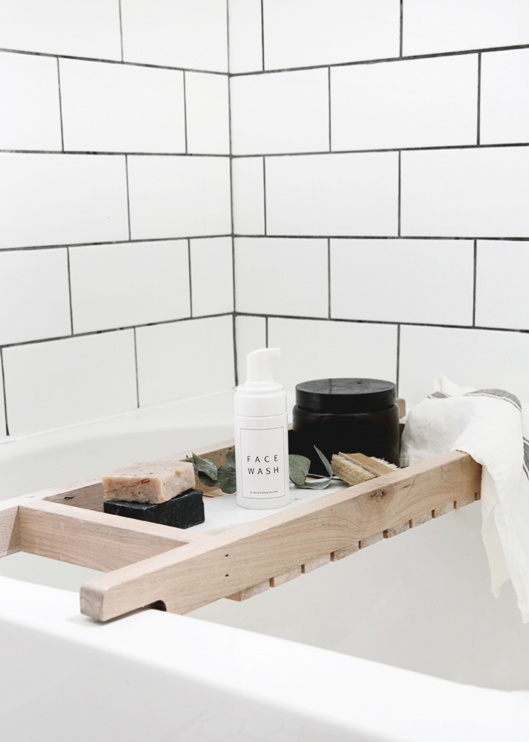 bottle of face wash on wood bathtub tray