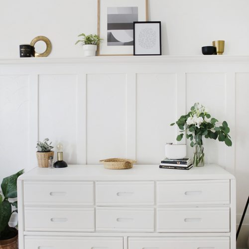 white dresser against white wall with flowers, plants, picture frames