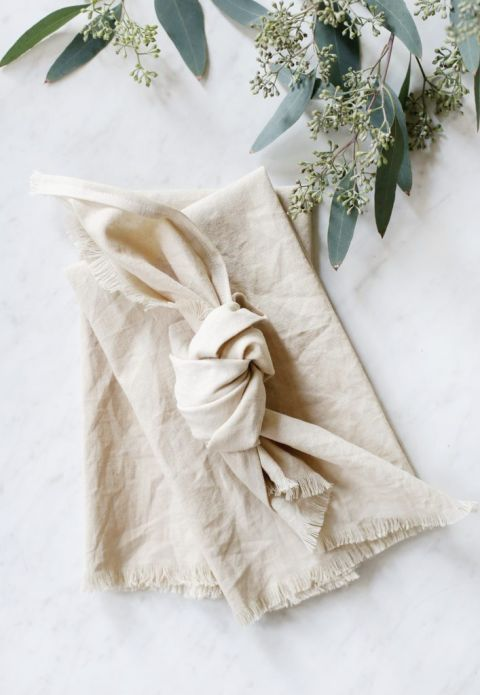 dyed linen napkins laid out on marble counter with eucalyptus