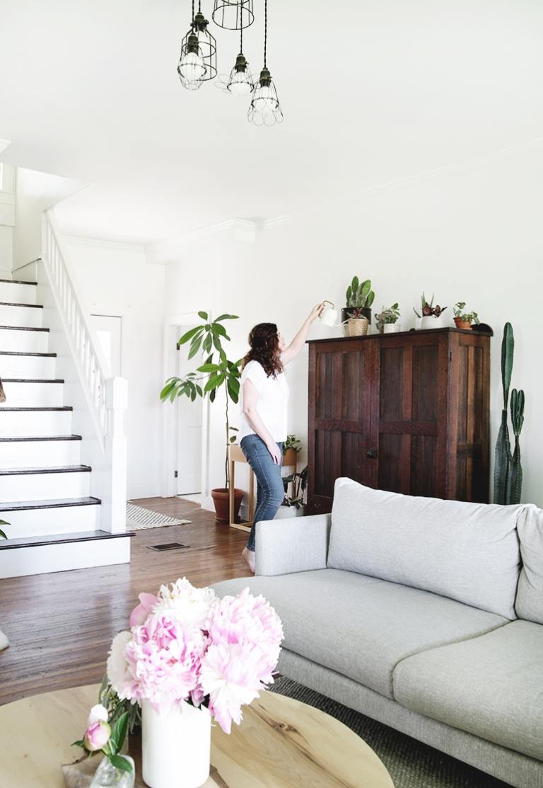 woman watering plants in living room