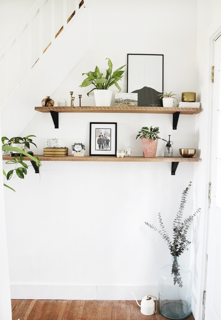 wood shelves with plants candles picture frames