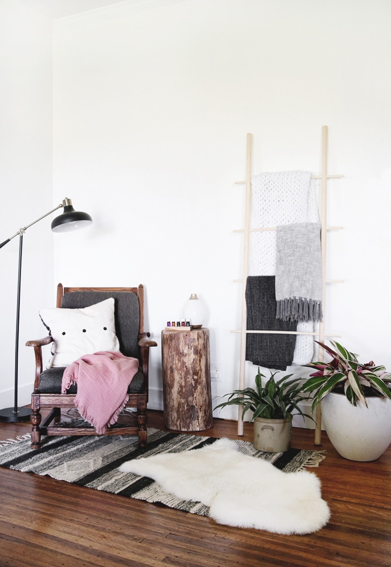 chair next to a blanket ladder and plants