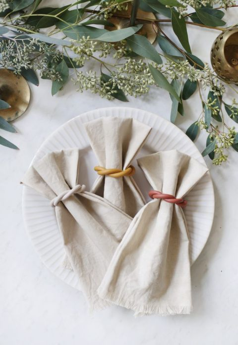 three napkins in napkin rings on a plate