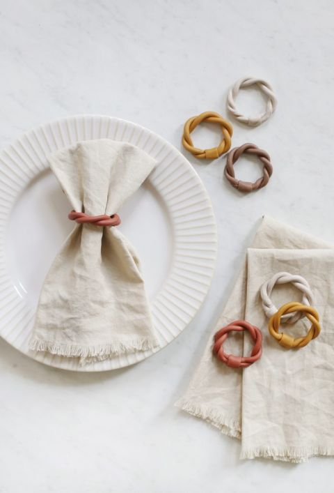 napkin in napkin ring on a plate next to stack of napkins and napkin rings