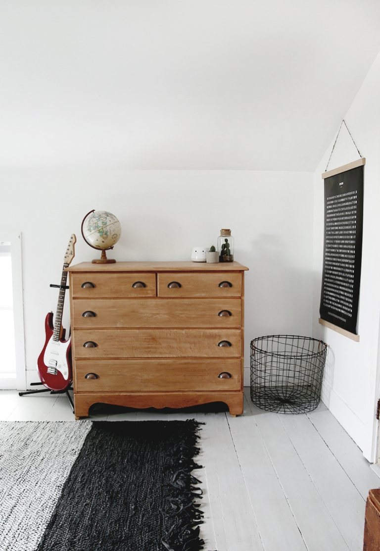 dresser with guitar and wire basket next to it
