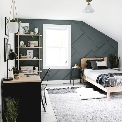 bedroom with blue wall with desk and bed