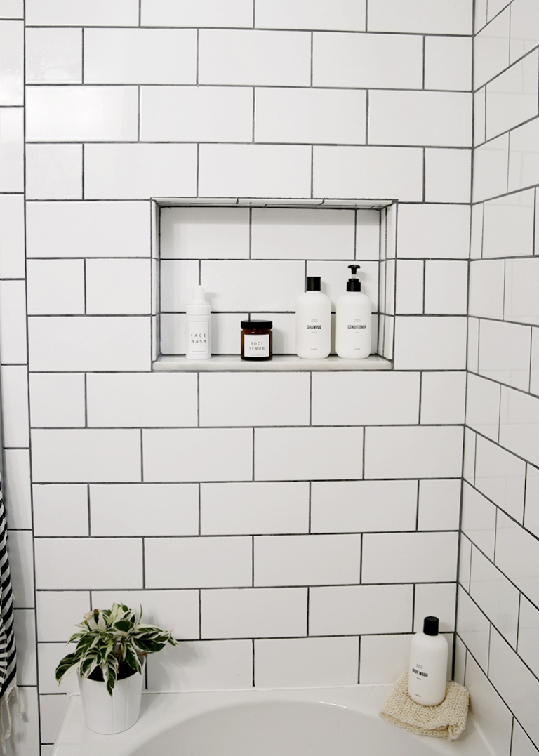 subway tile shower walls with shelf with shampoo bottles