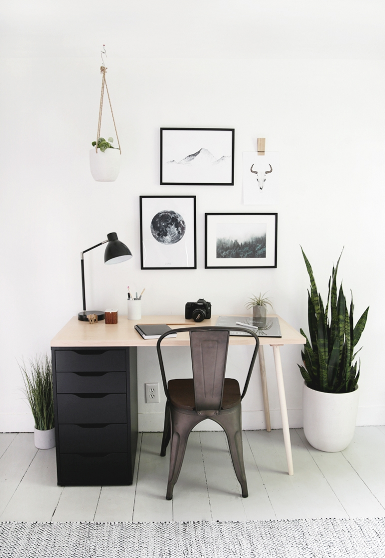 desk with black drawers and framed artwork above
