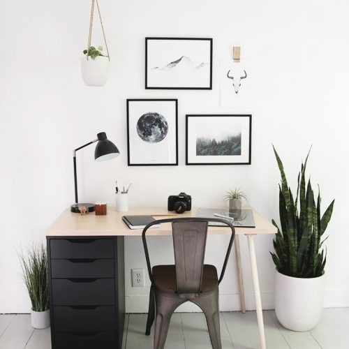 desk with black drawers and framed artwork above