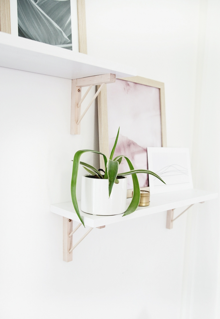white shelves with wood brackets styled with plants and prints