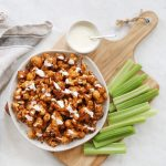 buffalo cauliflower on white plate with celery and blue cheese beside it