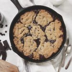 skillet brookie on towel with spatula next to it