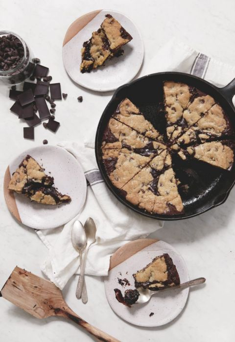 skillet cookie sliced next to plates with pieces of cookies on them