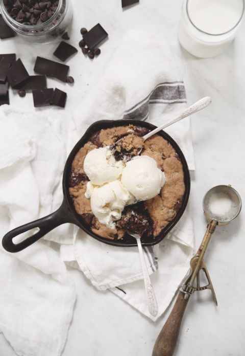 skillet brookie with ice cream on it and spoons in it