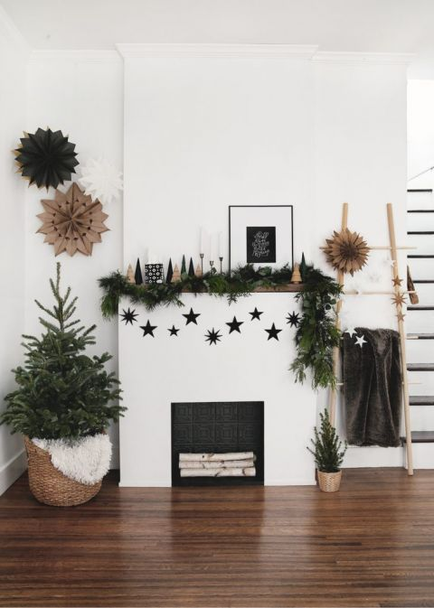 fireplace with holiday decor on mantel and small christmas tree in basket next to it