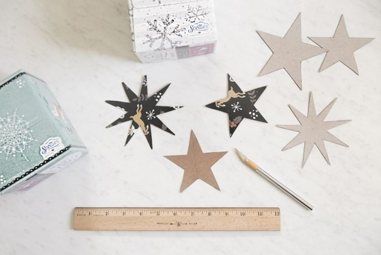 cardboard star cutouts next to ruler and x-acto knife