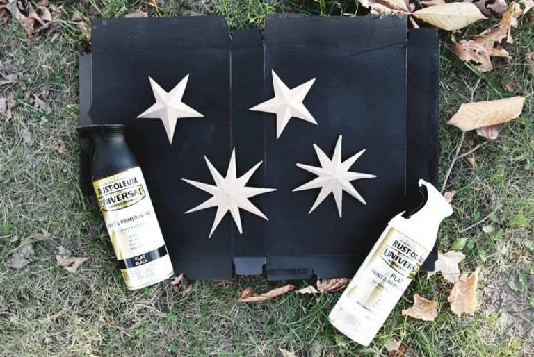 cardboard stars on black box with spray paint cans