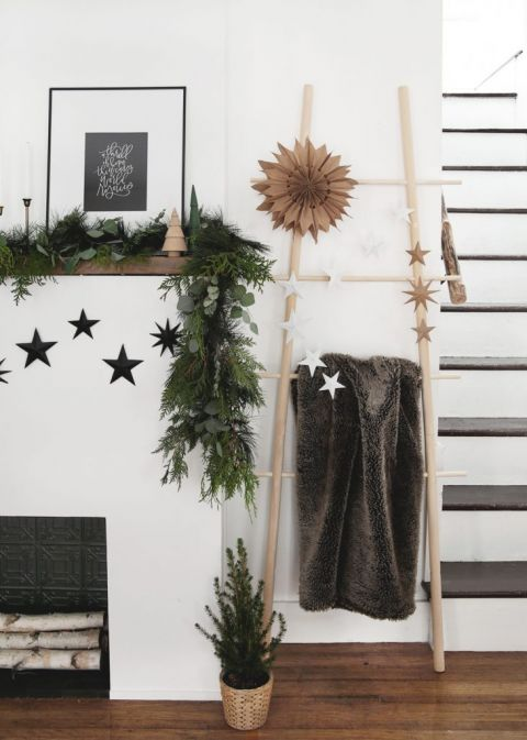 fireplace with blanket ladder next to it with 3D star decorations