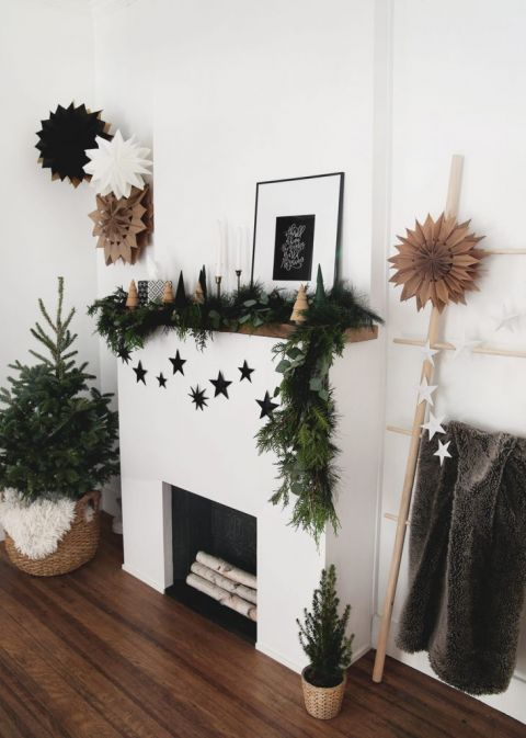 fireplace decorated with greenery garland, wood christmas tree and black 3D cardboard stars
