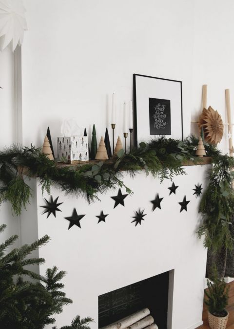 mantel with christmas decorations and black star garland