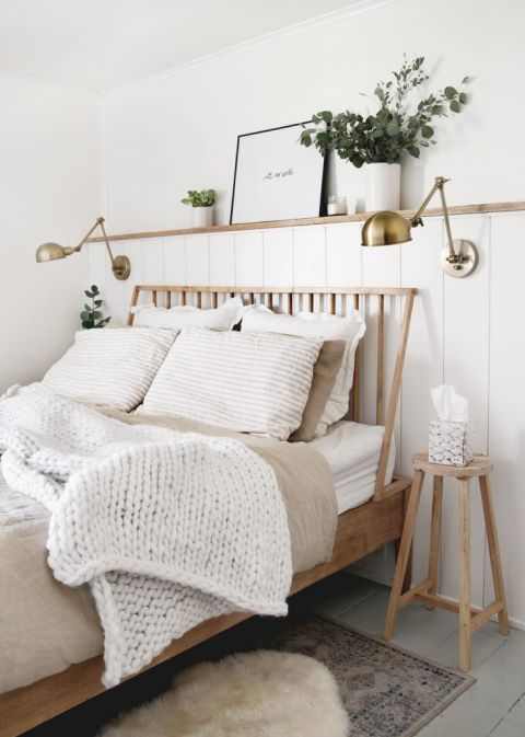 wood bed with white knit blanket on it with a stool next to bed