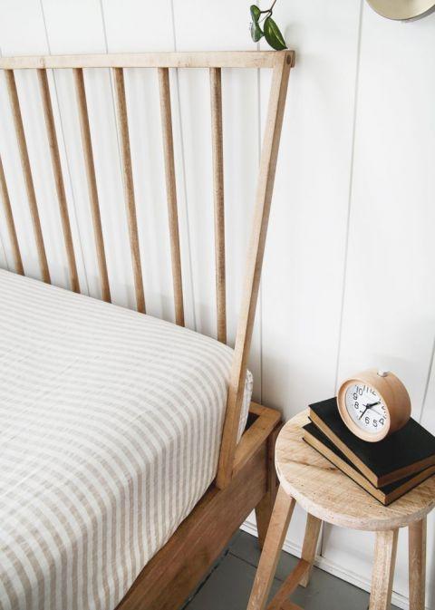 wood dowel headboard next to wood stool with clock on it