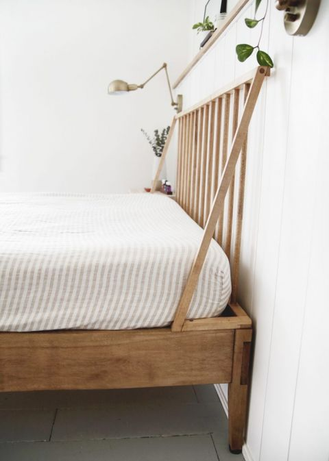 wood headboard and bedframe with striped sheet on bed
