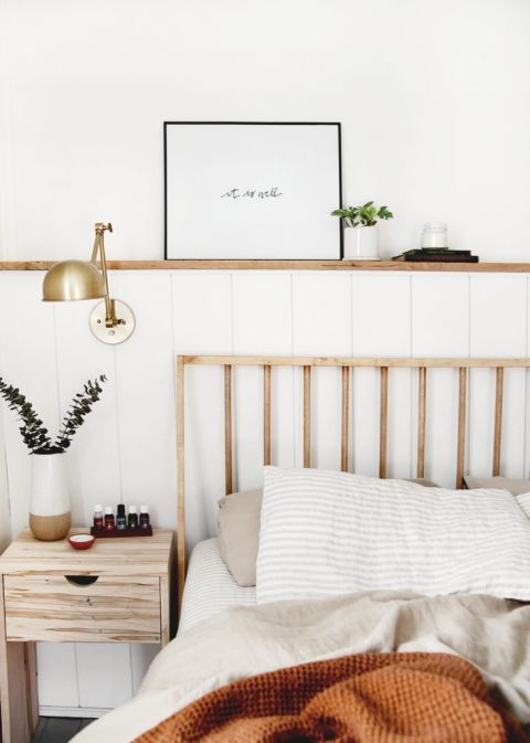bed next to wooden nightstand with shelf above bed
