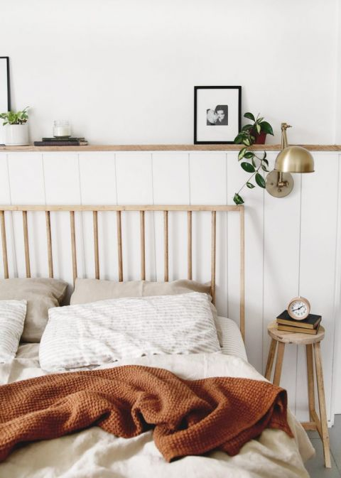 bed with wood stool night stand by brass lamp on wall