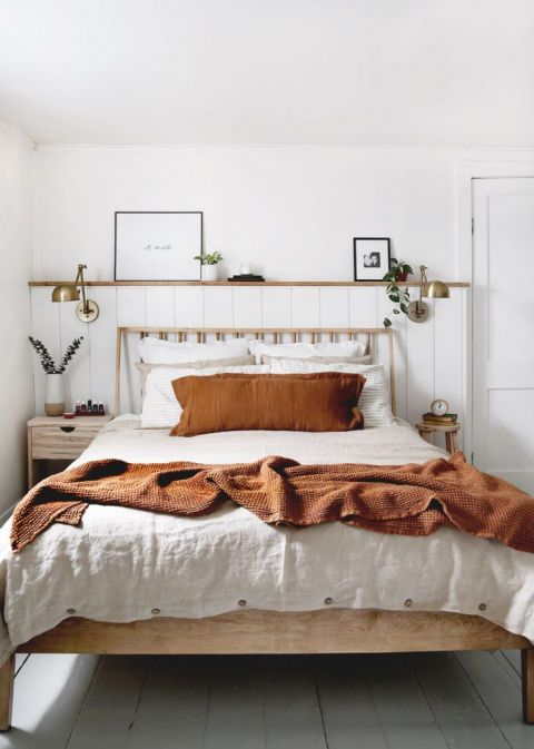 bed with rust color blanket on it with pillows and brass lamps on wall