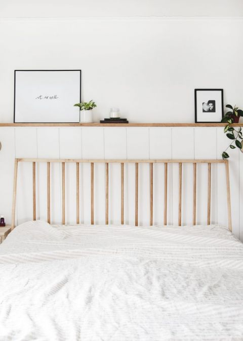 wood dowel headboard against white wall with wood shelf