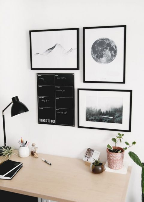 dry erase calendar hanging on wall above desk with art prints around it