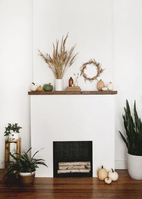 fireplace mantel with pumpkins and dried grass decor