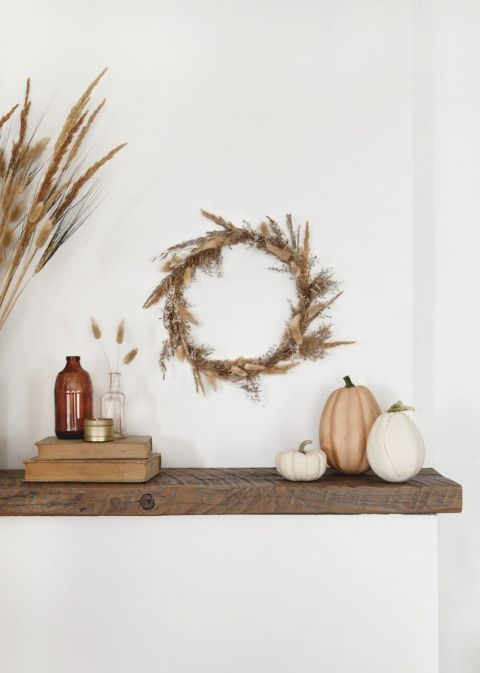 wood mantel with fall dried grass wreath and pumpkins