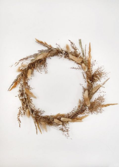 dried grass fall wreath hanging on white wall
