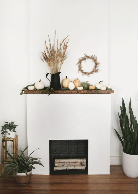 fireplace with dried grass and pumpkin decor