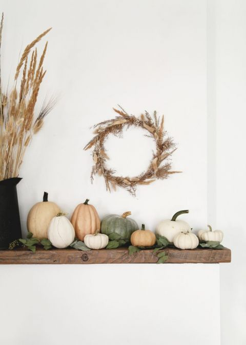 wood mantel with pumpkins and dried grass wreath